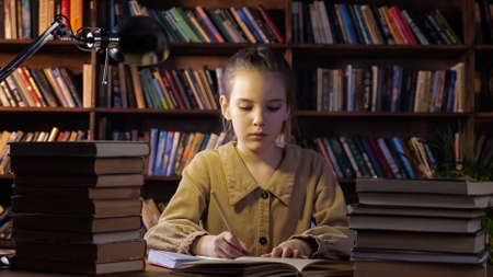 Exhausted young lady writes home assignment in copybook with brown pencil sitting among different books at home in late evening closeup