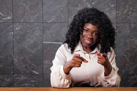 Afro-american businesswoman in white blouse waves hand and talks gesticulating promoting actively new project conducting blog in new office Standard-Bild