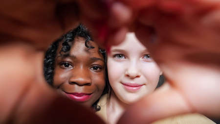 Black stepmother with curly hair and blonde adopted schoolgirl show heart sign with hands and look into eyes with joyful smiles closeup