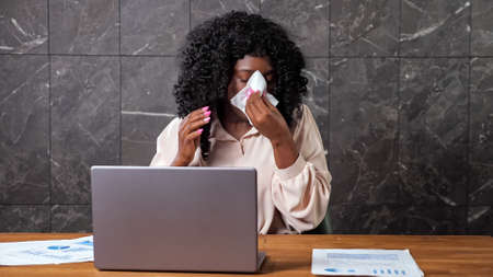 Tired Afro-american company worker lady with curly hair sneezes into paper napkin and puts palm on forehead near grey laptop, at office with marble wall Foto de archivo