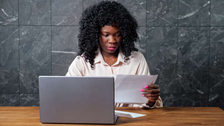 Stressed Afro-american businesswoman opens envelope with bank letter and enters code on grey laptop keyboard on wooden table against marble office wall