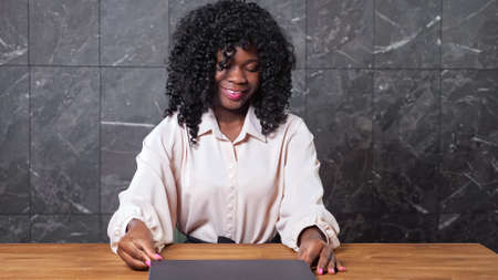 Young African-American woman in elegant light blouse happy of finished work smiles closing laptop at table near grey wall in office closeup