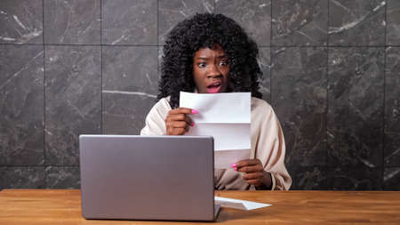 Black businesswoman opens envelope with bank letter and shocked shakes head with negative reaction sitting at table with laptop by grey marble wall Standard-Bild