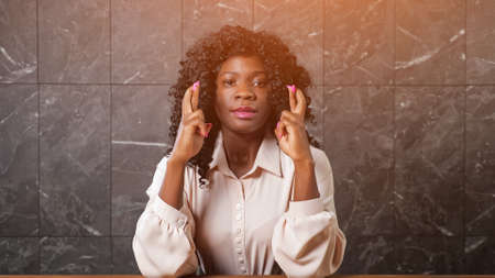 Worried black lady in blouse holds crossed fingers of trembling hands and smiles with happiness sitting at office table at grey marble wall, sunlight Foto de archivo