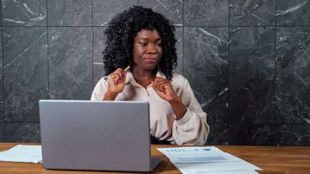 Thoughtful worried black businesswoman with curly hair looks around sitting at grey laptop with sheets of papers and gnawing pen in office