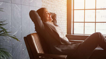 Delighted businesswoman with short dark hair sits down falling on brown bench with happy smile in office reception against large windowt, sunlight