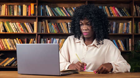 Attractive young African-American woman in stylish shirt writes notes looking into contemporary laptop sitting at table near bookshelves