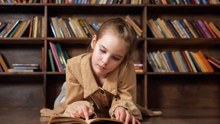 Concentrated young lady reads book preparing for online lesson at wooden table against bookshelves at coronavirus pandemic isolation