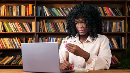 African-American teacher shows cards with letters to laptop camera at online English lesson sitting at table against bookshelves at home
