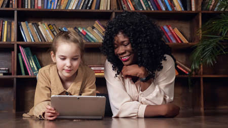 Black woman with long loose curly hair looks into tablet display sitting near young blonde lady and smiling against books in library closeup Foto de archivo