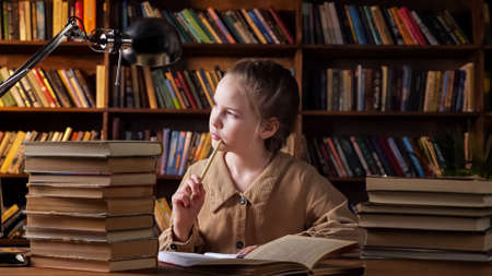Thoughtful schoolgirl writes home task in paper notebook sitting at table with book stacks and black lamp against large bookshelves at night