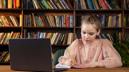 Young lady in pink blouse looks at laptop screen and writes in copybook sitting at wooden table against coloured books on shelves in library Foto de archivo