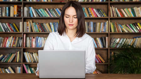 Concentrated young woman in stylish white blouse works with papers near contemporary laptop at table against large library racks full of book Foto de archivo
