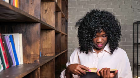 Cheerful African-American woman in stylish blouse takes book from wooden shelf to prepare for test in contemporary library close view