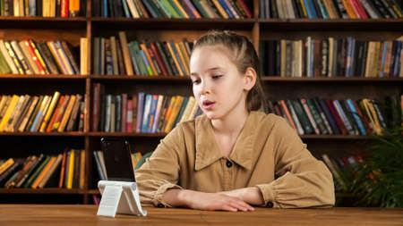 Schoolgirl blogger talks sitting at brown wooden desk and looking into black smartphone on white support display against bookshelves in library