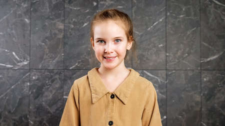 Funny cheerful schoolgirl in brown dress looks straight and smiles standing against grey marble wall with white natural patterns closeup