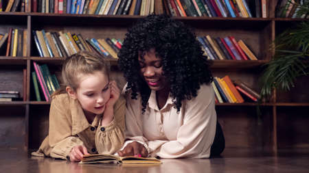 Individual black woman tutor with long curly hair teaches blonde schoolgirl sitting at table and reading book against brown wooden racks in library closeup Foto de archivo