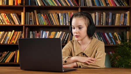 Lady junior student in black headphones listens to teacher and answers sitting at wooden table with grey laptop against racks of books