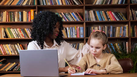 Black lady hugs sad adopted blonde girl sitting at brown table with grey laptop and writing in copybooks against racks with books at online lesson Foto de archivo