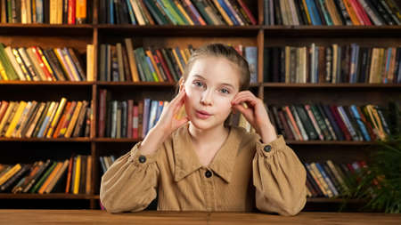 Young lady in brown jacket raises hand and answers teacher questions at online lesson sitting at table against racks with different coloured books