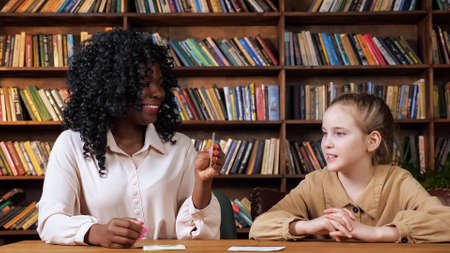 Individual black tutor teaches blonde schoolgirl letters with special flashcards sitting at table against racks with books at covid isolation