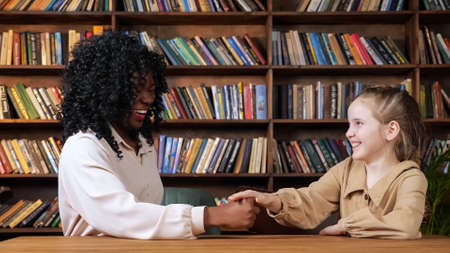 Afro-american lady with long loose curly hair and blonde schoolgirl play rock paper scissors and laugh sitting in library against books on racks Foto de archivo