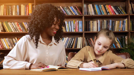 Professional individual Afro-American tutor with long curly hair dictates text to blonde schoolgirl and junior student writes sitting in library Standard-Bild