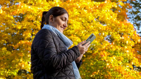 Young woman writes a message on the phone against the background of yellow trees. Standard-Bild
