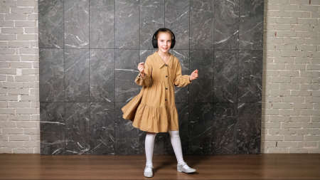 Delighted active girl in brown dress dances wearing black headphones against designed marble wall surrounded by grey bricks in hallway Standard-Bild