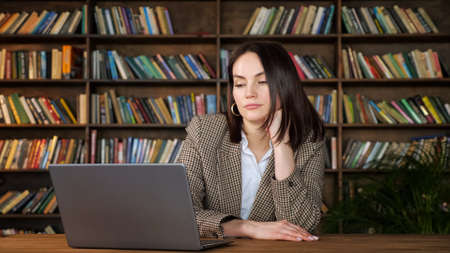Bored brunette with short loose hair looks into grey laptop display holding head on hand at brown table against bookshelves in office