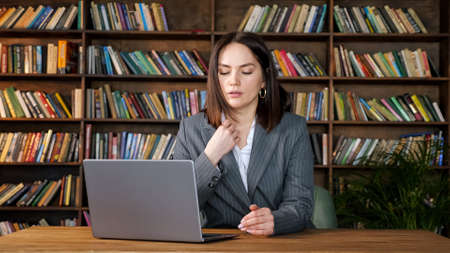Professional secretary in grey costume types on laptop sitting under strong fan wind against different coloured books on racks in office Standard-Bild