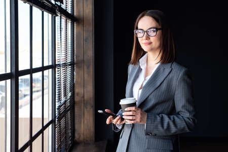 Beautiful business woman with phone and coffee stands by the window.