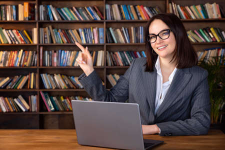 Woman in formal suit sitting at table with laptop pointing to copy space.