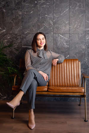 young woman sits on a leather armchair in formal clothes, a variant of an office wardrobe.