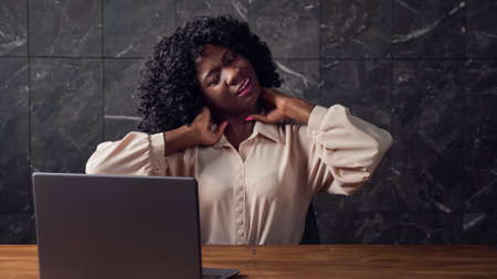 Bored Afro-american secretary with curly hair stretches back sitting at brown wooden table with grey laptop by marble wall in empty office
