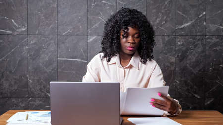 Black businesswoman in white blouse gathers papers looks through and types on laptop sitting at brown wooden table in office with marble wall