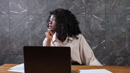 Afro-american company manager woman with curly hair sits at table with laptop and papers looking out window in office with marble wall