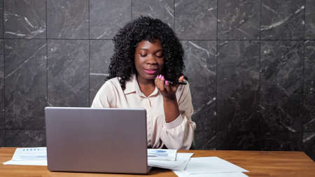 Afro-american businesswoman with curly hair talks on smartphone and looks at graphs on papers sitting at desk with laptop against marble wall