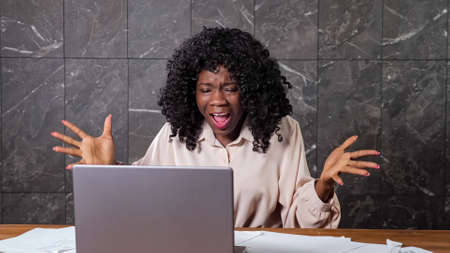 Angry black businesswoman with curly hair shouts at company workers during online conference sitting at brown wooden table with laptop