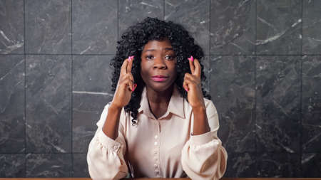 Worried black lady in blouse holds crossed fingers of trembling hands and smiles with happiness sitting at office table at grey marble wall Standard-Bild