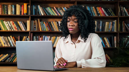 African-American businesswoman with headphones takes part at online conference via laptop sitting at table against library bookshelves slow motion