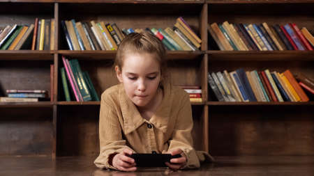 Interested schoolgirl plays online game on black smartphone sitting at brown table against large bookcase staying home at pandemic isolation