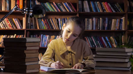 Concentrated girl in brown jacket writes homework in paper notebook with pencil sitting under lamp light among books in library at night