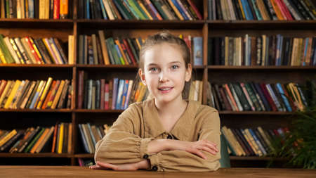 Serious young lady in brown dress looks straight and smiles cheerfully to camera sitting at wooden table against library bookshelves Standard-Bild