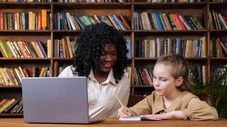 Black woman tutor and blonde schoolgirl give each other high five after performing difficult home task at table with laptop and copybooks at quarantine