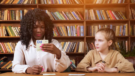 Professional black teacher repeats letters with young lady showing flashcards against brown wooden racks with books at home covid lockdown, sunlight Standard-Bild