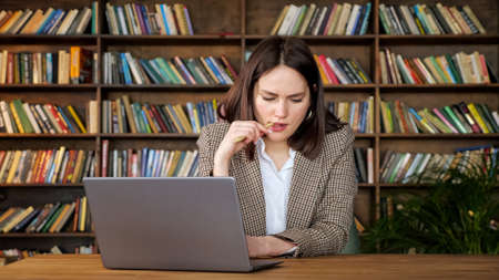 Thoughtful female project manager holds pen looking at laptop display and types sitting at brown table against wooden bookshelves in office Foto de archivo