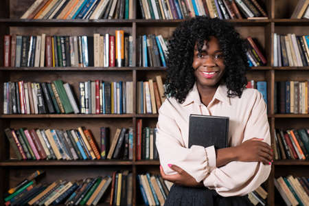 Young african american woman with a book in hands on the background of shelves with books, copy space.