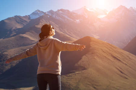 young brunette woman stands with her arms outstretched on a background of snow-capped mountain peaks, sunlight. Foto de archivo