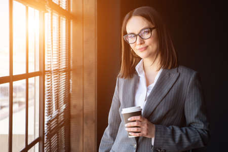 Beautiful business woman with coffee stands by the window, sunlight.